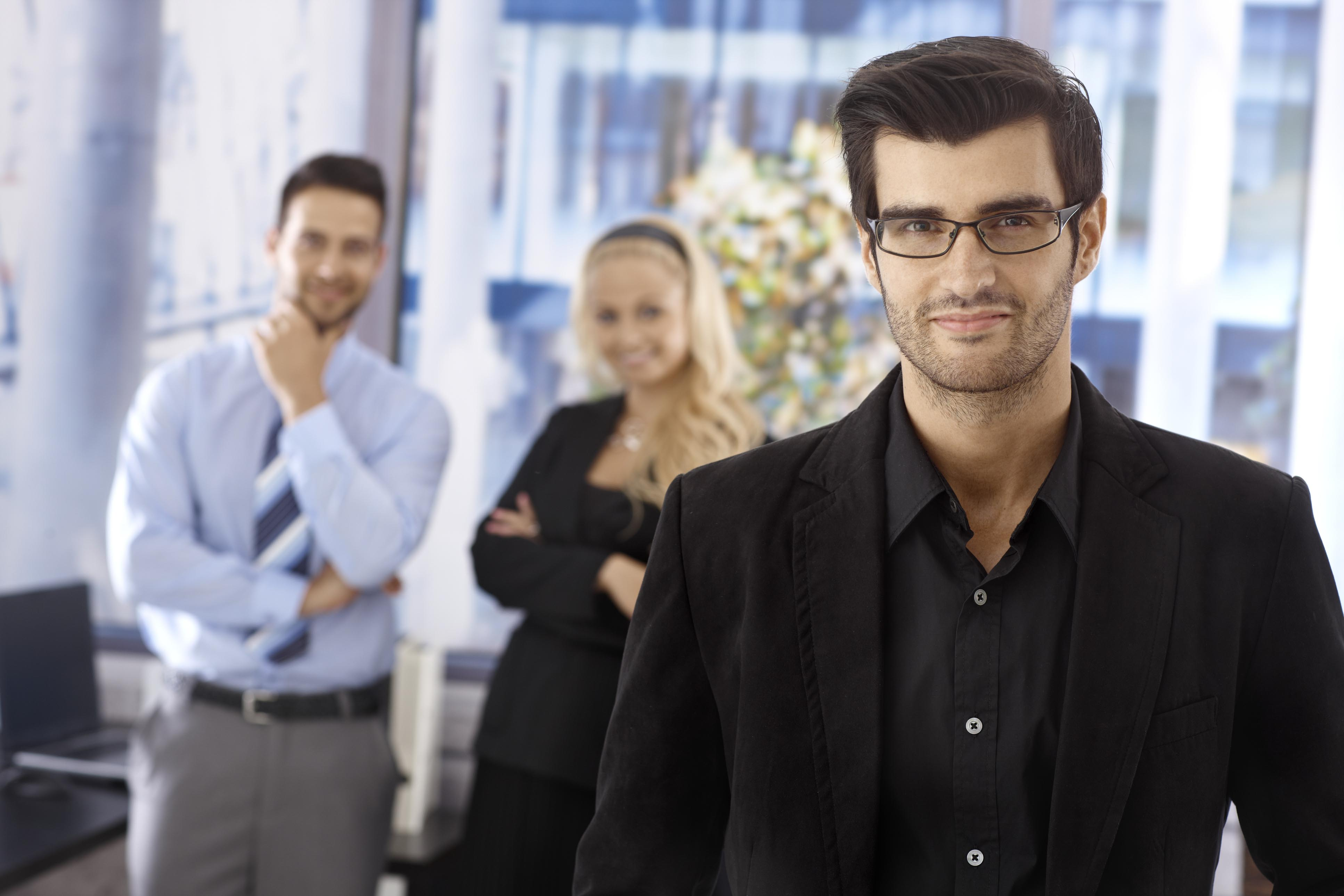 A man with glasses and two collegues in background thinking about how they can develop or train their employees.