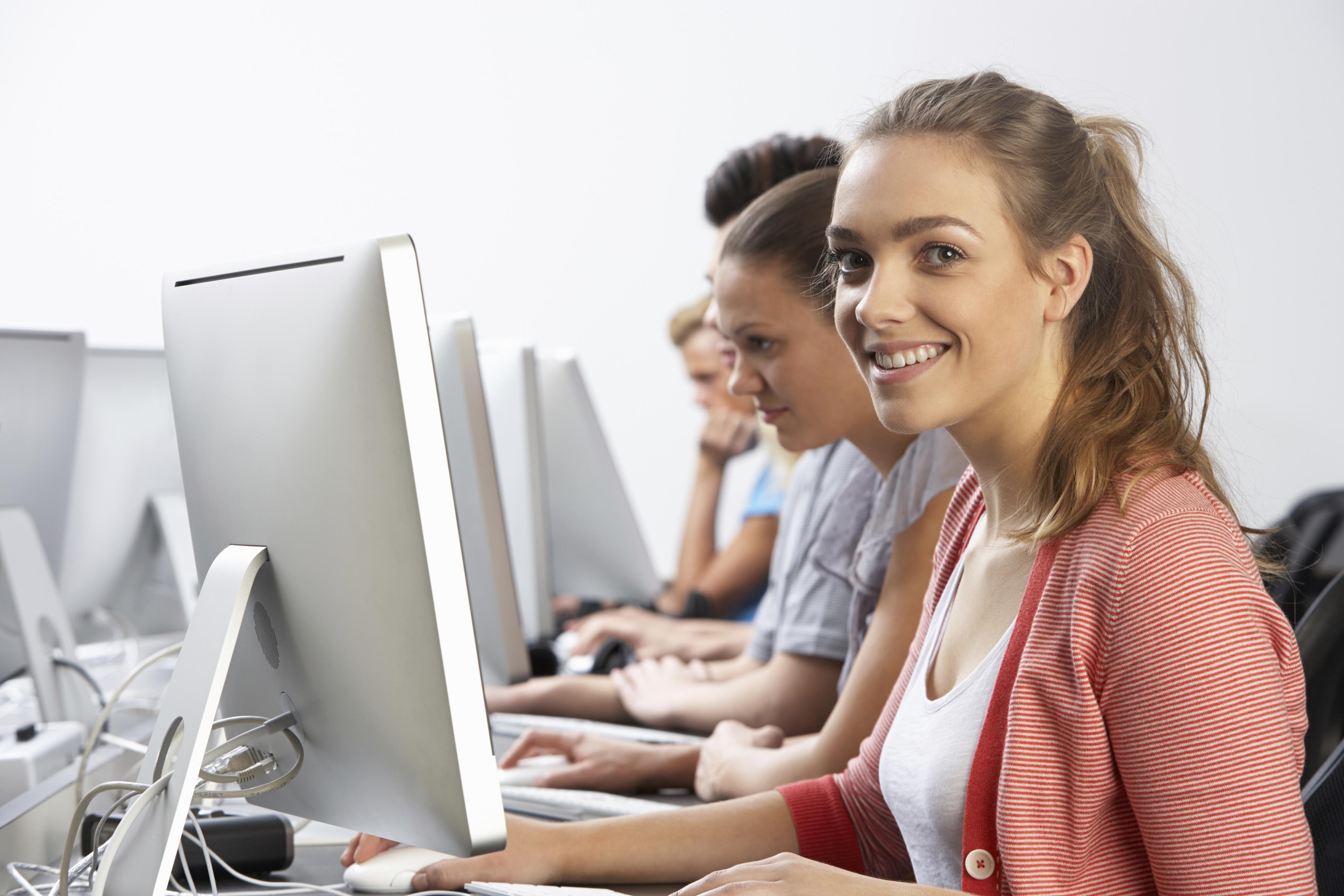 Girl smiling and classmates in background in a computer class.