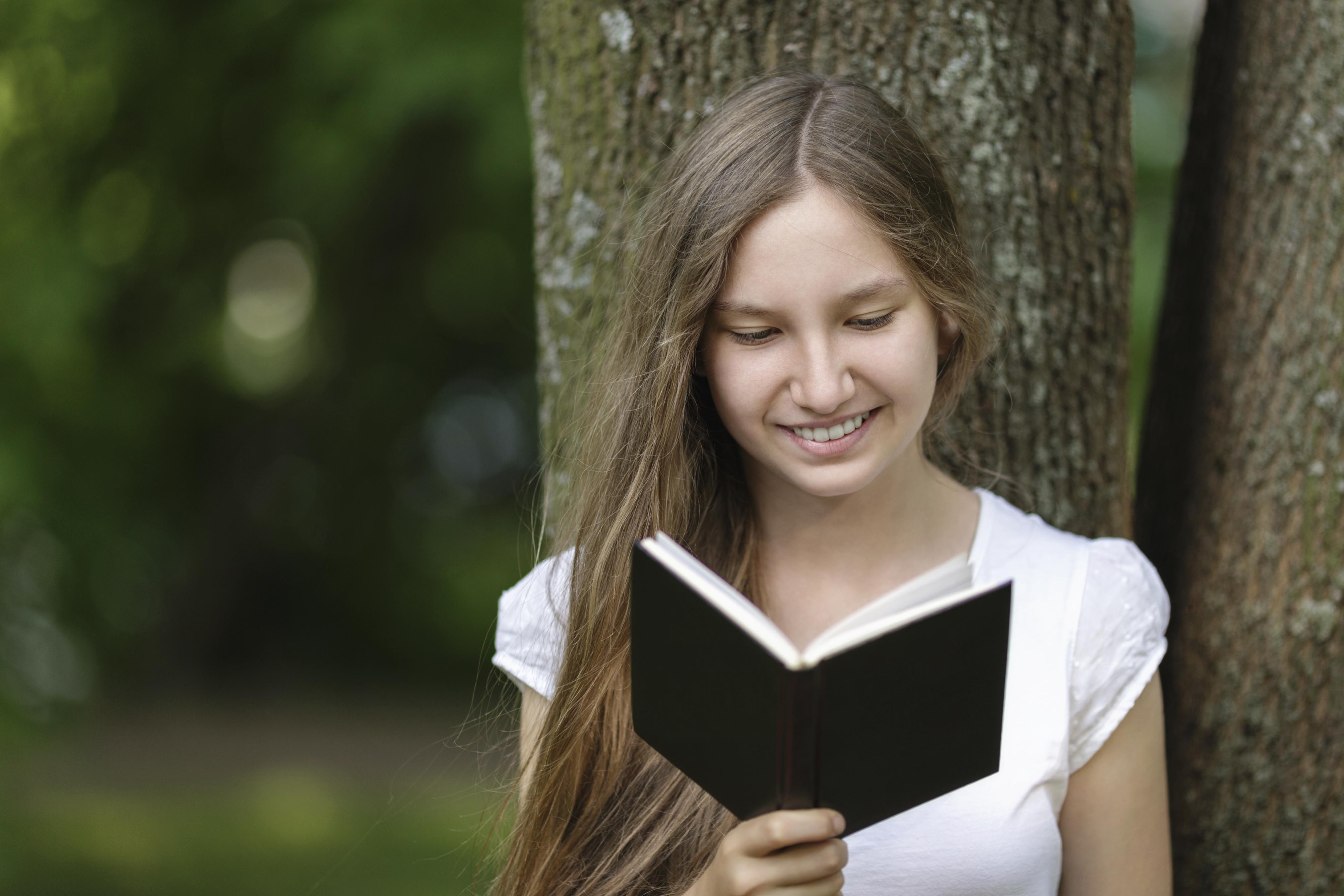 A female student reading a black book.